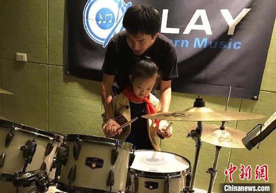 图为王一木指导小朋友学习架子鼓。 受访者供图