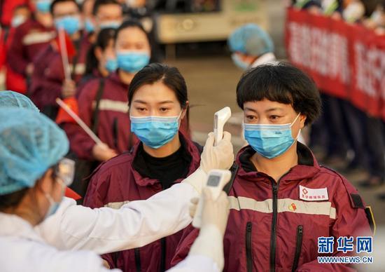 ↑3月18日,在重庆江北国际机场,工作人员为重庆援鄂医疗队首批返回的医护人员检测体温。