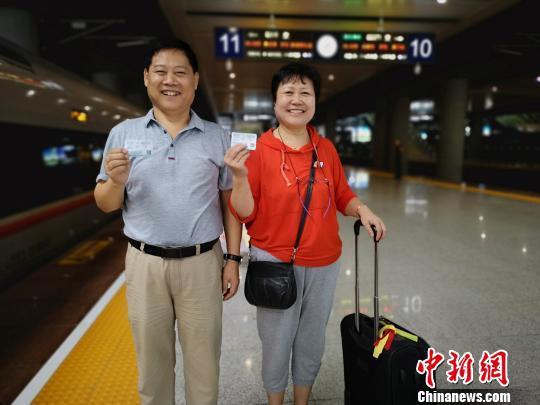66岁的刘国建在6月就买好了前往香港的动车票,要带着妻子和岳母一起乘坐高铁到香港旅游。图为刘国建与妻子在始发站重庆西站合影。 韩璐 摄