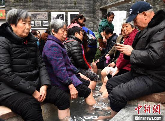 图为市民在露天温泉泡脚驱寒。 周毅 摄