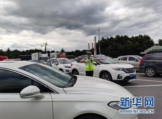 国庆期间,高速执法人员在水江服务区疏导交通。新华网发