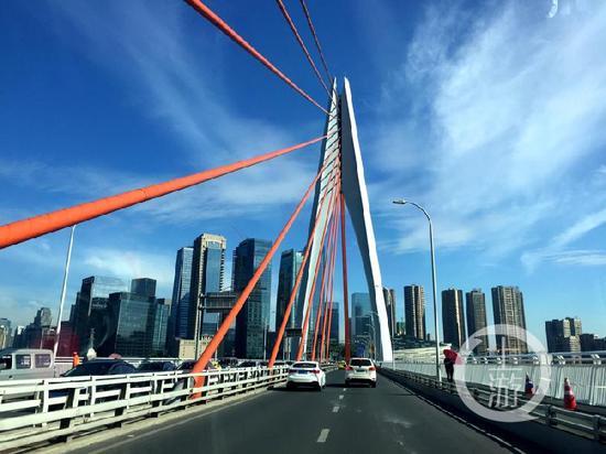 △25日,千厮门大桥上在蓝天白云的映衬下格外美丽。上游新闻记者 邹飞 摄