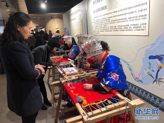 图为培训班学员在展览现场刺绣。新华网 陶玉莲 摄