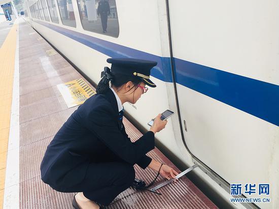 黔江火车站工作人员精心测量动车与站台间距 新华网发(黄松 摄)