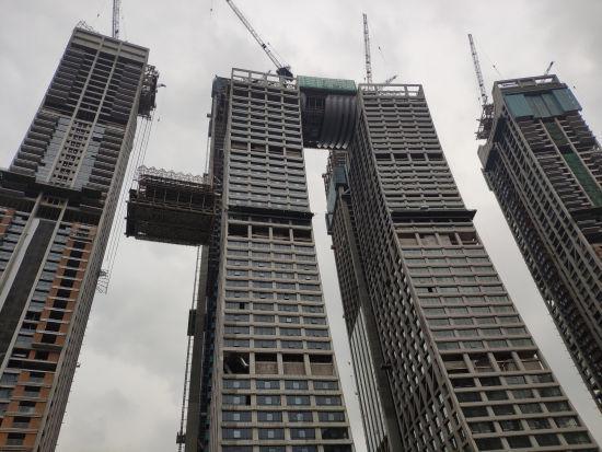 """资料图为重庆来福士""""横向摩天楼""""正在吊装 受访者供图"""