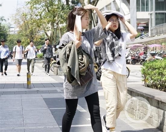 △大学城,学生们用手和书遮挡烈日。