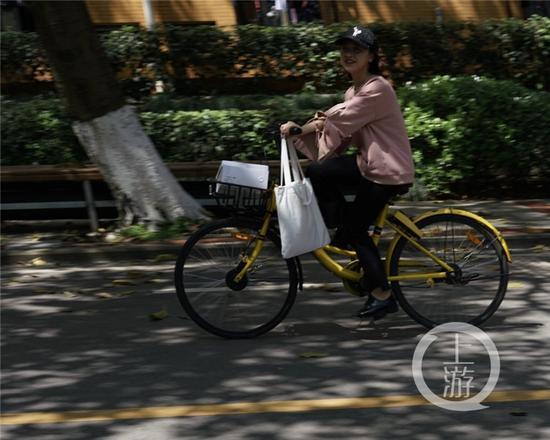 △大学城,学生在树荫下骑行。