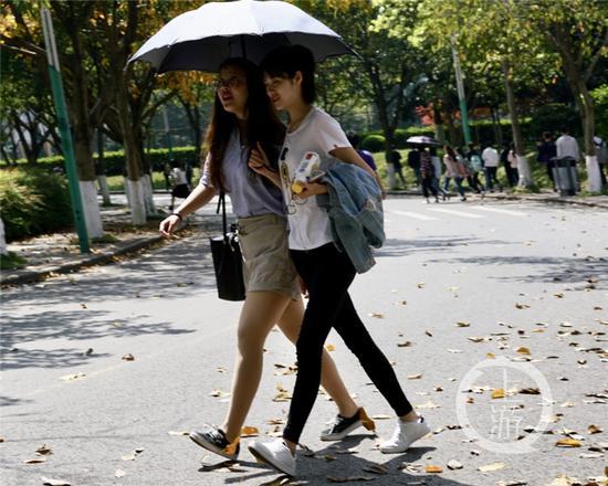 △大学城,人们用太阳伞遮挡烈日。