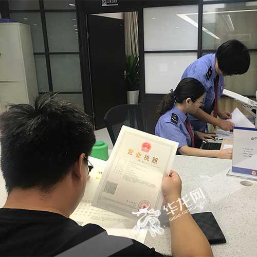 乔智杰在看刚办下来的营业执照 见习记者张琦 摄
