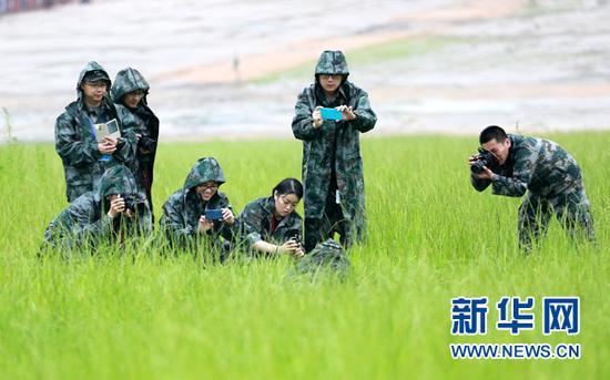 图为网络媒体国防行记者编辑冒雨拍摄特战旅的战士。(中国经济网裴小阁 摄)