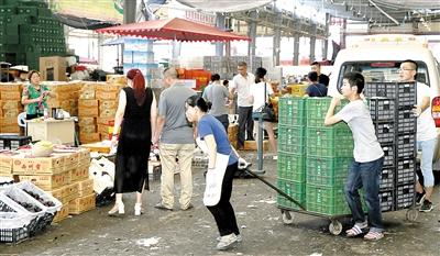 双福水果市场里一片繁忙的景象。