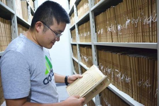 合川档案馆信息技术科科长杨旭渊帮慢新闻-重庆晚报记者查询文献档案