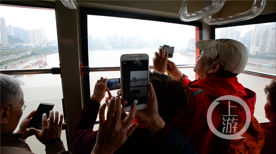 △外地游客在索道缆车上拍摄重庆风光