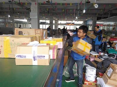 渝东北快递物流分拨中心内,工作人员忙碌着,把数以千计包裏进行分拨。