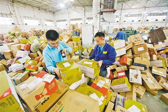 11月14日,重庆EMS公司邮件处理中心,工作人员正在快递堆里扫描信息。
