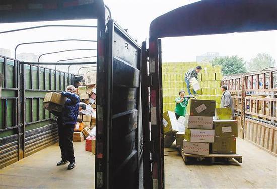 11月14日,重庆EMS公司邮件处理中心外停满了满载快递的货车,工作人员正抓紧时间卸载快递。