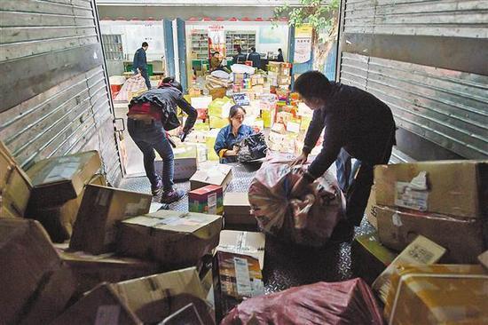 11月14日,EMS公司人和营业部,快递员正在分拣包裹。