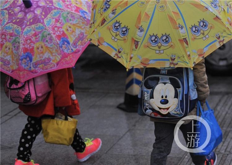 冬日的清晨,细雨纷飞,上班一族步履匆匆的踏过淅沥的街头,他们中间夹着不少矮小些的伞花--------小学生也是清晨街头的主角。