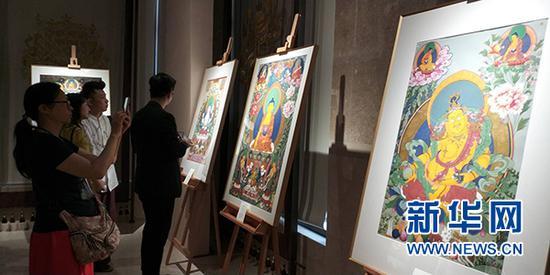 """""""五彩祥云——西藏唐卡艺术lovebet app首展""""现场,游客拿出手机拍摄唐卡作品。新华网发(主办方供图)"""