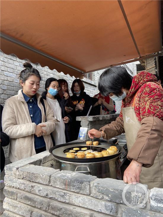 △市民在山城巷排队买小时候常吃的熨斗糕