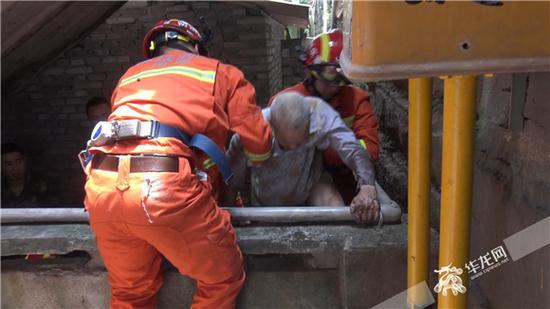 消防官兵搀扶老人翻越栏杆,回到院坝。涪陵消防供图 华龙网发