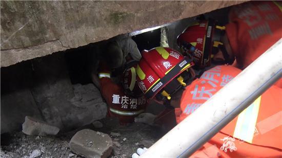 在消防官兵的帮助下,老人成功从下水道中脱困,并走出楼梯。涪陵消防供图 华龙网发