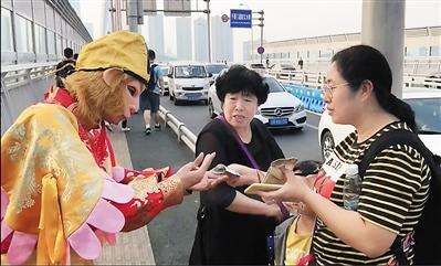 """11日,""""孙悟空""""合影后伸手向游客要钱。 本报记者 李斌 摄"""