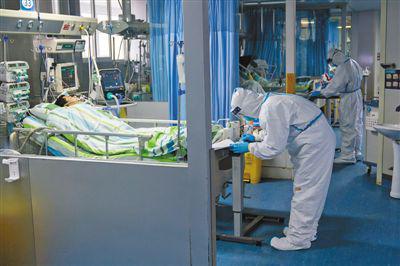 1月24日,在武汉大学中南医院重症隔离病房,医护人员正在为病人治疗。     新华社记者 熊 琦摄