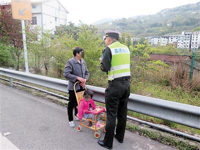 执法人员将中年妇女带离高速公路。 高速执法供图