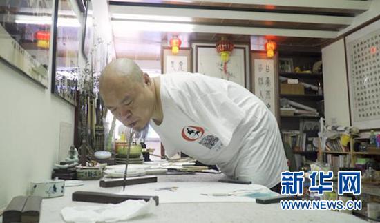 黄国富正在作画。新华网 彭博 摄