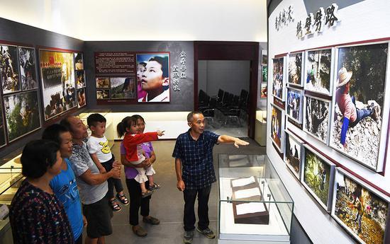 ↑7月3日,下庄村村主任毛相林(右一)在下庄精神陈列馆内讲述当年修路的故事。新华社记者 王全超 摄
