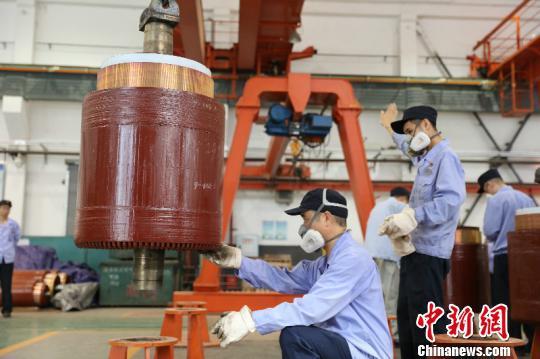 图为重庆机务段电枢组职工将烘焙了16小时候,温度达到达165℃至175℃的电枢吊到检修存放架上。 李富彬 摄