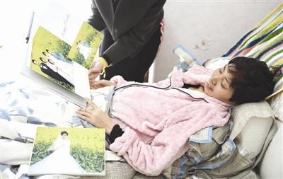 付建蓉躺在床上看照片 摄影记者 张士博