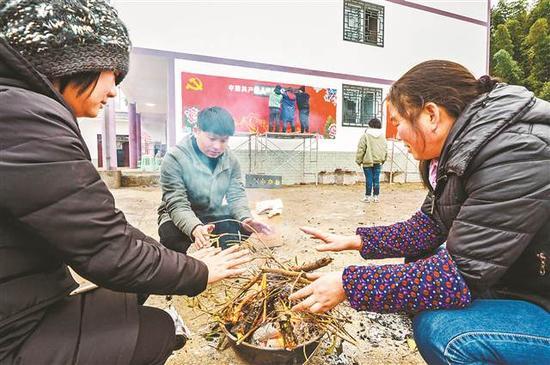 村民在室外支起一个烤火炉,方便师生取暖。