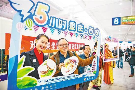 12月6日,乘客在重庆北—西安北的首发动车前合影留念。