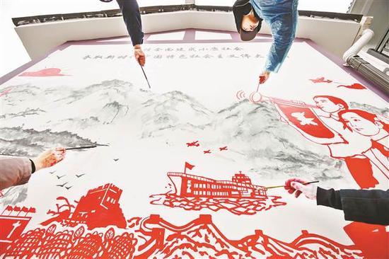 武隆区土坎镇清水村村民活动中心,天空飘着雨夹雪,室外最低气温仅1℃。此时,四川美术学院的师生在墙上作画。