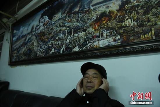 一位重庆大轰炸受害者听取通报情况。 中新社记者 陈超 摄