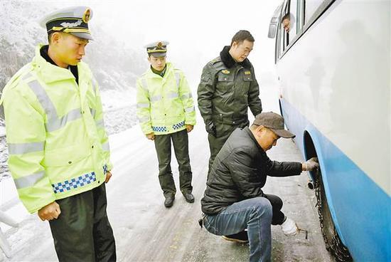 酉阳 1月4日,酉阳,交通运管人员上路督查驾驶员安装防滑链。通讯员 陈碧生 摄