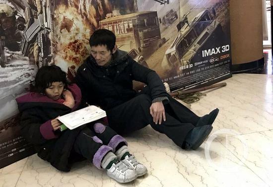 △11日下午,观音桥华谊影院旁,棒棒王中正坐地上等活,他刚上小学一年级的侄女王双宝躺在地上写作业。