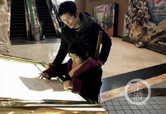 △王宝双在一广告台上写作业。