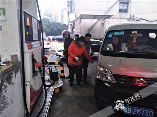 加油员赵伟向记者指明当初白色长安车加油的位置。记者张勇 摄