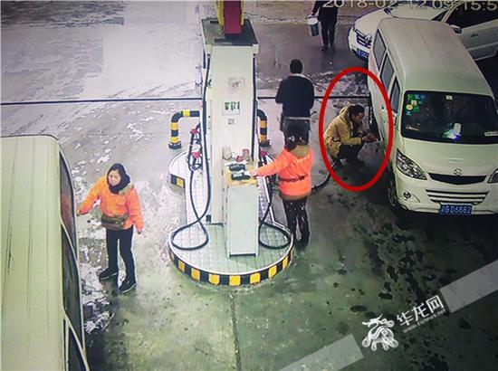 熊某蹲在地上加油,加油员赵伟在一旁看着。记者张勇 摄
