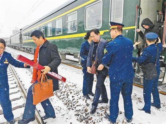 铁路客运乘务员正在转运大雪受阻列车上的乘客。(受访者供图)