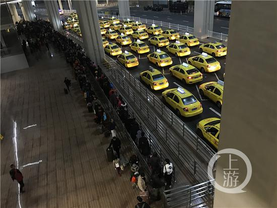 今年春节期间,T3航站楼出租车上客点人多车多的情形