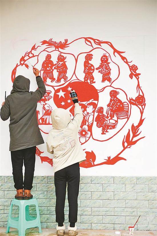 师生在墙上创作以剪纸、年画为表现形式,展现新农村风貌的画作。