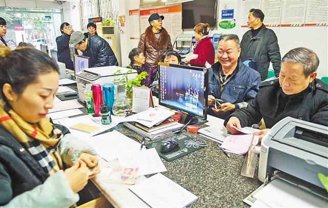 一月十五日,大渡口区跃进村街道革新社区,老年人在社区工作人员帮助下办理老年卡。