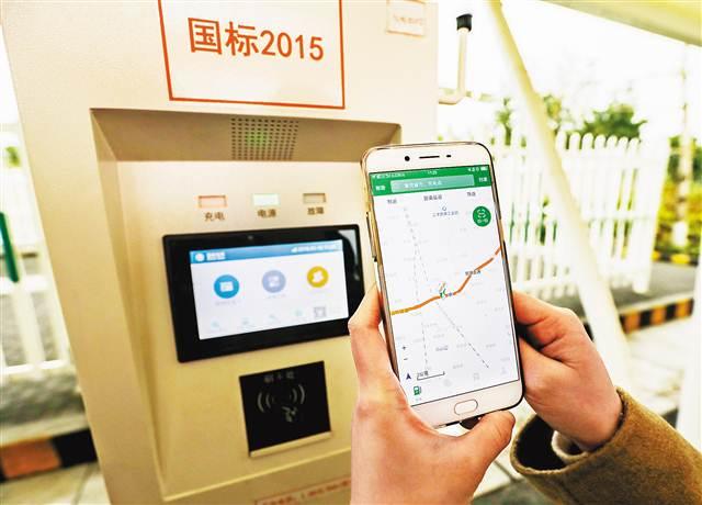 1月16日,重庆绕城高速珞璜服务区电动汽车充电站内,一名重庆市民体验用软件充电的流程。