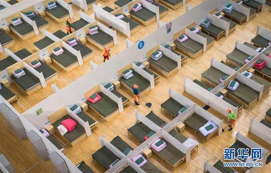 2月12日,在武汉体育中心方舱医院,工人在进行整理和清洁工作(无人机照片)。 新华社记者 肖艺九 摄