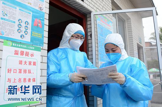 左丽(右)与医生核对发热病人基本情况登记表。新华网发(张常伟 摄)