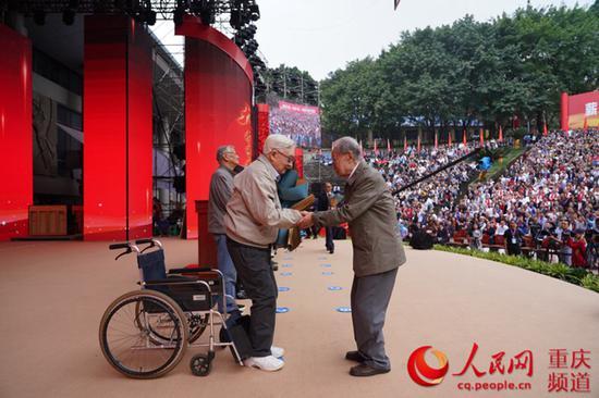 95岁高龄的学生献花,94岁的老师坚持从轮椅上站起来接受献花。邹乐摄
